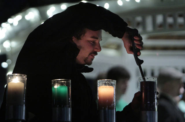 OU senior Matthew Lorch lights menorah candles at the University of Oklahoma�s holiday lights celebration in Norman.