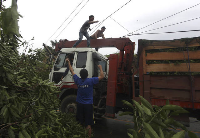 Workers clear a highway of toppled trees after Typhoon Bopha made a landfall in Compostela Valley in southeastern Philippines Tuesday Dec. 4, 2012. A Philippine governor says at least 33 villagers and soldiers have drowned when torrents of water dumped by the powerful typhoon rushed down a mountain, engulfing the victims and bringing the death toll from the storm to about 40. (AP Photo/Karlos Manlupig)