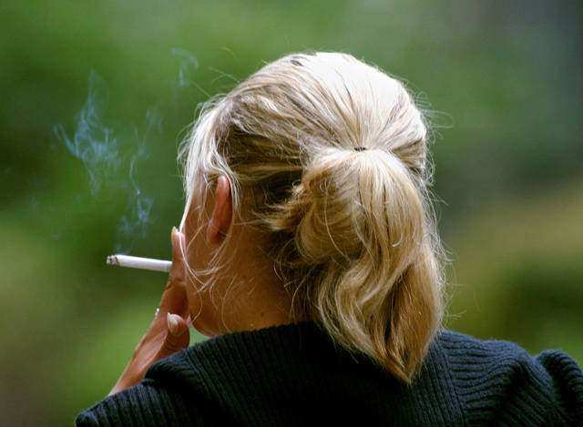 A woman smokes a cigarette during a break from work in downtown Chicago. New research finds that women who smoke today have a much greater risk of dying from lung cancer than they did decades ago compared to those who never smoked. AP FILE PHOTO