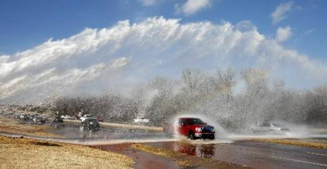 Vehicles try to navigate a water main break that shot water across all six lanes of the 7400 block of the NW Expressway in Oklahoma City Monday, Dec. 3, 2012. Photo by Paul B. Southerland