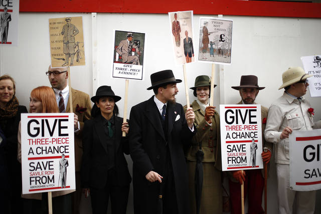 People take part in a protest outside the proposed location the U.S. clothing retailer Abercrombie & Fitch propose to open a children's store on Savile Row, the traditional men's bespoke tailoring street, in the Mayfair district of London, Monday, April 23 , 2012. The protest on Monday was organised by The Chap magazine, a publication for English gentlemen whose manifesto includes always wearing tweed and cultivating interesting moustaches. (AP Photo/Matt Dunham)
