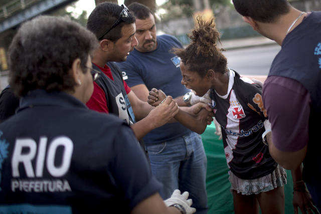 In this photo taken Nov. 22, 2012, an alleged crack addict, second from right, tries to bite a social worker as she is taken to a nearby shelter in Rio de Janeiro, Brazil.  While some people go meekly, many fight, cry, scream out in desperation in their altered states. Once they're gone, their paltry belongings, ratty mattresses, pans, sweaters, are swept up by a garbage removal company. With a boom in crack use over the past decade, Brazilian authorities are struggling to help such users and stop the drug's spread, sparking a debate over the legality and efficiency of forcibly interning users. Adults can't be forced to stay in treatment, and most leave the shelters within three days. (AP Photo/Felipe Dana)