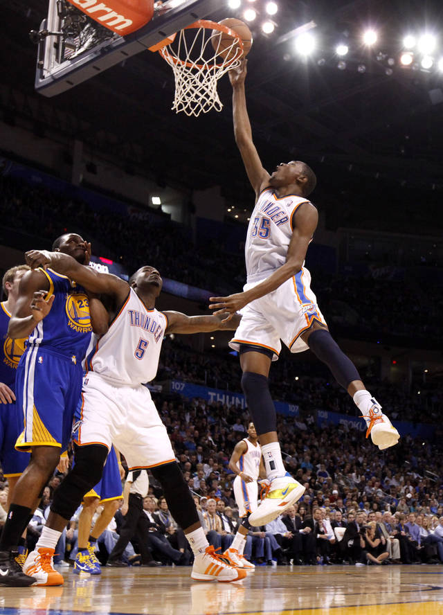 Oklahoma City's Kevin Durant (35) goes to the basket beside Oklahoma City's Kendrick Perkins (5) and Golden State's Al Thornton (23) during the NBA basketball game between the Oklahoma City Thunder and the Golden State Warriors at the Oklahoma City Arena, Tuesday, March 29, 2011. Photo by Bryan Terry, The Oklahoman