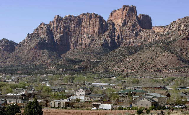 FILE - Hildale, Utah sits at the base of red rock cliff mountains with its sister city, Colorado City, Ariz., in the foreground in this Thursday, April 20, 2006, file photo. A federal appeals court ruled Monday, Nov. 5, 2012, that the polygamist sect on the Utah-Arizona border waited too long to challenge a court-ordered takeover, clearing the way for state authorities to break up a church trust and sell assets including homes, businesses and farms in two small towns. A three-judge panel of the 10th U.S. Circuit Court of Appeals overturned a federal judge in Salt Lake City, who ruled nearly two years ago that Utah's takeover violated the constitutional rights of the Fundamentalist Church of Jesus Christ of Latter-Day Saints. (AP Photo/Douglas C. Pizac, File)