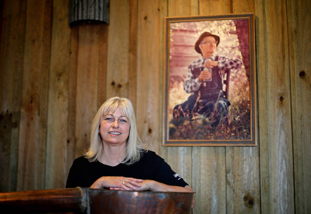 In this Friday, Nov. 16, 2012 photo, entrepreneur Cheryl �Happy� Wood stands under a portrait of her grandfather Simmie Free in the Dawsonville Moonshine Distillery, in Dawsonville, Ga. Distillers are making their first batches of legal liquor in this tiny Georgia town's hall, not far from the mountains and the maroon, orange and gold canopy of trees that once hid bootleggers from the law. (AP Photo/David Goldman)