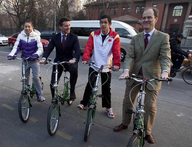 "From left, Yang Yilin, gymnastic gold medalist of the 2008 Beijing Olympic, Sebastian Coe, chairman of the London Organizing Committee of the Olympic and Paralympic Games, Lin Furong, paralympic swimmer, and Sebastian Wood, British Ambassador to China, riding their bicycles with words ""Green Games, Green Future"" arrive to the British Embassy in Beijing, China, Sunday, Dec. 11, 2011. Coe arrives the embassy to give a press briefing on an update on preparations for the London 2012 Olympics and Paralympic Games. (AP Photo/Andy Wong)"