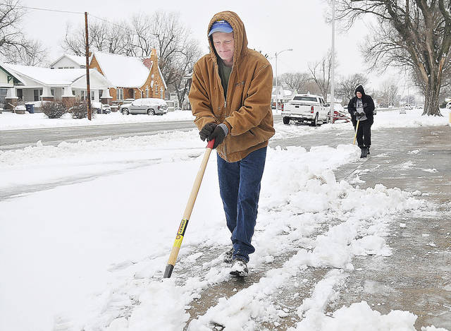 Chris and Deana Momsen shovel snow from a parking area along E Broadway  in Enid on Monday.  Photo by Billy Hefton, Enid News & Eagle/AP