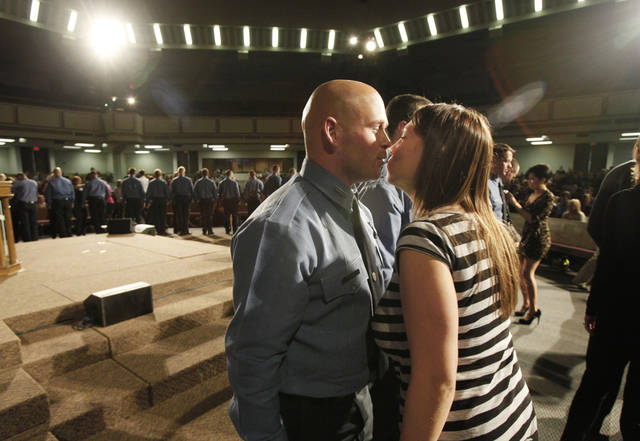 Oklahoma City firefighter Bobby Atkinson gets a kiss from his wife Kristen after she pinned his badge on during Oklahoma City Fire Department's recruit  class of 2011-12  graduation at Crossroads Church in Oklahoma City, Friday, February 10, 2012. The class had 29 recruits graduating from the training class. Photo By Steve Gooch, The Oklahoman