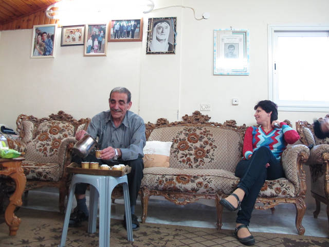 In this April 11, 2012 photo, Palestinian Ali Khatib, left, pours coffee in his home in the village of Shaab in northern Israel, where photos of his ancestors are displayed, as a woman watches. Khatib's family was split by Israel's creation, spreading his relatives to Syria, Denmark, Canada and Saudi Arabia. Social media have produced a boom in communications between Palestinians in Israel and the Arab world, once connected only through rare letters carried by intermediaries or the International Red Cross. Some Palestinians are finding their way back to each other through social media that know no borders. (AP Photo/Ben Hubbard)
