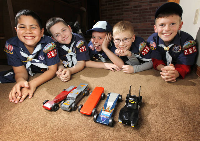 From left, Cub Scouts Caden Hardridge, 9, Xavier Gass, 8, Jake Ward, 8, Ben Geimer, 8, and Matthew Rapson, 8, pose for a photo with their pinewood derby cars in Nicoma Park, Okla., Thursday, Feb. 16, 2012. Photo by Nate Billings, The Oklahoman