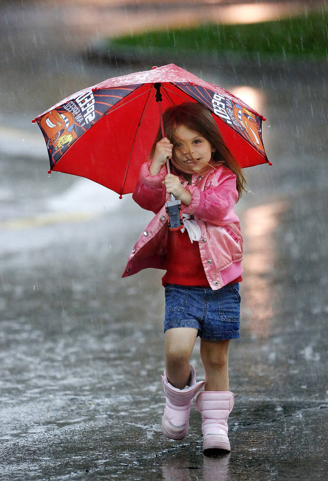 Rylee Rigsby, 3 1/2, is prepared as she caught in an afternoon deluge while leaving the library in Midwest City. She has her own umbrella and is wearing rain boots. Her grandmother said she had been excited all day about going to the library so she wasn't going to let thunderstorms prevent  the pair from making the visit.  Strong thunderstorms, producing heavy downpours and lightning moved through the Oklahoma City area  during the morning and early afternoon hours on Saturday, Oct. 13, 2012. Overcast skies and intermittent rain continued throughout the day.    Photo by Jim Beckel, The Oklahoman