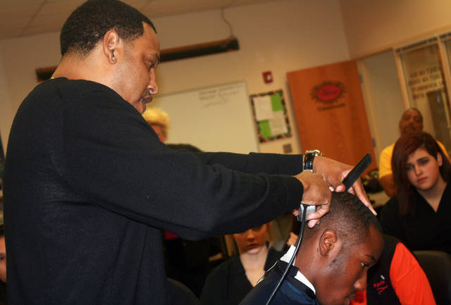 Corey Sutter demonstrates a haircut on the head of Canadian Valley Technology Center student Shawn Anderson. Sutter owns Fade N Up Barber Shop in Oklahoma City.  PHOTO PROVIDED BY CANADIAN VALLEY TECHNOLOGY CENTER