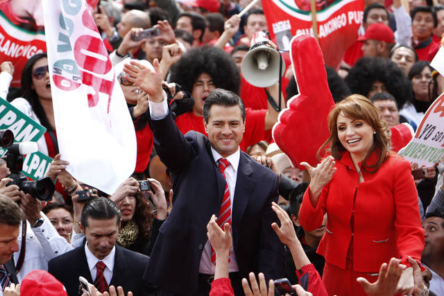 Enrique Pena Nieto, former governor of Mexico State and the unopposed presidential candidate for the Institutional Revolutionary Party, PRI, and his wife, Mexican actress Angelica Rivera, right, acknowledge the cheers of supporters during a rally in Mexico City, Sunday Nov. 27, 2011. Pena Nieto filed his nomination papers Sunday, for the July 2012 presidential election at party headquarters. Pena Nieto, who has led in all the recent national polls, seeks to regain the presidency the PRI lost in 2000 after 71 years in power. (AP Photo/Marco Ugarte)