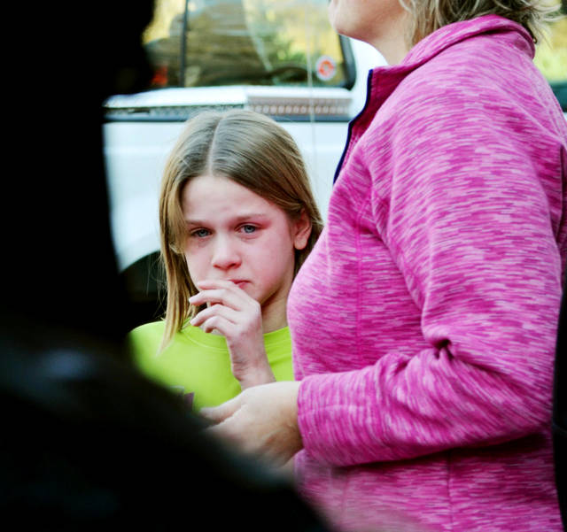 A young girl cires following a shooting at the Sandy Hook Elementary School in Newtown, Conn., about 60 miles (96 kilometers) northeast of New York City, Friday, Dec. 14, 2012. A gunman entered the school Friday morning and killed at least 26 people, including 20 young children. (AP Photo/The New Haven Register, Melanie Stengel)  ORG XMIT: CTNHR107