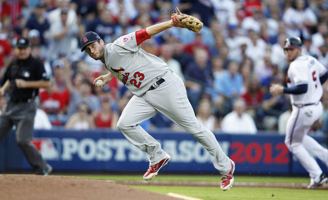 St. Louis Cardinals third baseman David Freese (23) picks up a bunted ball hit by Atlanta Braves' David Ross during the third inning of the National League wild card playoff baseball game on Friday, Oct. 5, 2012, in Atlanta. Ross was safe at first base. (AP Photo/John Bazemore)