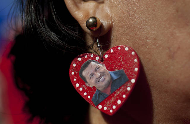 "A supporter of Venezuela's President Hugo Chavez wears earrings she decorated with an image of Chavez as she attends a rally in Caracas, Venezuela, Thursday, Jan. 10, 2013. The government organized the unusual show of support for the cancer-stricken leader on the streets outside Miraflores Palace on what was supposed to be his inauguration day. Chavez has been fighting an unspecified type of pelvic cancer since June 2011 and has undergone repeated surgeries, chemotherapy and radiation treatments. The government said in its last update on Monday that Chavez was in a ""stable situation"" while being treated for a severe respiratory infection. The government has hasn't said how severe his ""respiratory deficiency"" is. (AP Photo/Ariana Cubillos)"