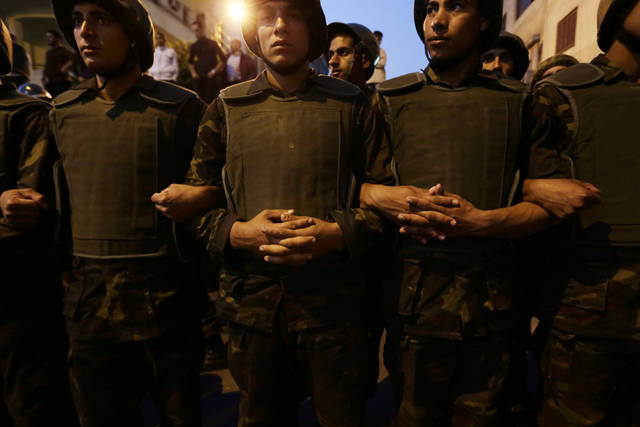Egyptian army soldiers stand guard near the presidential palace in Cairo, Egypt, Sunday, Dec. 9, 2012. Egypt's liberal opposition called for more protests Sunday, seeking to keep up the momentum of its street campaign after the president made a partial concession overnight but refused its main demand he rescind a draft constitution going to a referendum on Dec. 15. (AP Photo/Hassan Ammar)