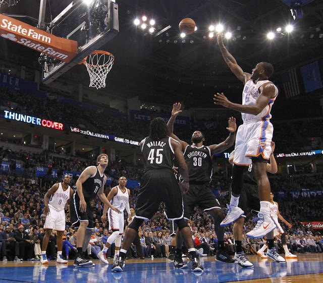 Oklahoma City's Kendrick Perkins (5) puts up a shot over Brooklyn Nets' Gerald Wallace (45) and Reggie Evans (30) during the NBA basketball game between the Oklahoma City Thunder and the Brooklyn Nets at the Chesapeake Energy Arena on Wednesday, Jan. 2, 2013, in Oklahoma City, Okla. Photo by Chris Landsberger, The Oklahoman