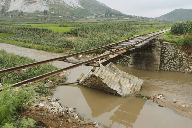 <p>In this July 30, 2012 photo, a bridge supporting railway lines is destroyed after heavy rain in Onchon County, North Korea. The rain Sunday and Monday followed downpours earlier this month that killed nearly 90 people and left more than 60,000 homeless, officials said. The floods also come on the heels of a severe drought, fueling renewed food worries about a country that already struggles to feed its people.(AP Photo/Jon Chol Jin)</p>