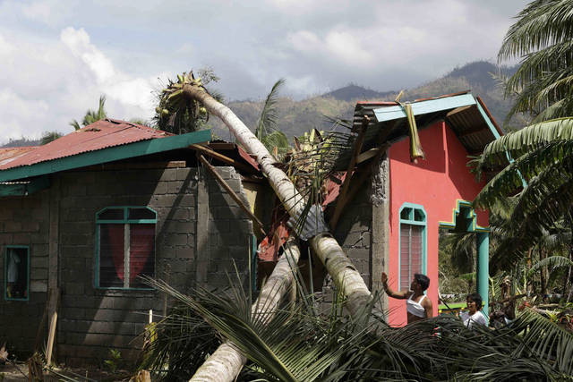 A couple look at their house damaged by Tuesday's devastating typhoon, Thursday, Dec. 6, 2012, in New Bataan township, Compostela Valley in the southern Philippines.  The powerful typhoon that washed away emergency shelters, a military camp and possibly entire families in the southern Philippines has killed hundreds of people with nearly 400 missing, authorities said Thursday. (AP Photo/Bullit Marquez)