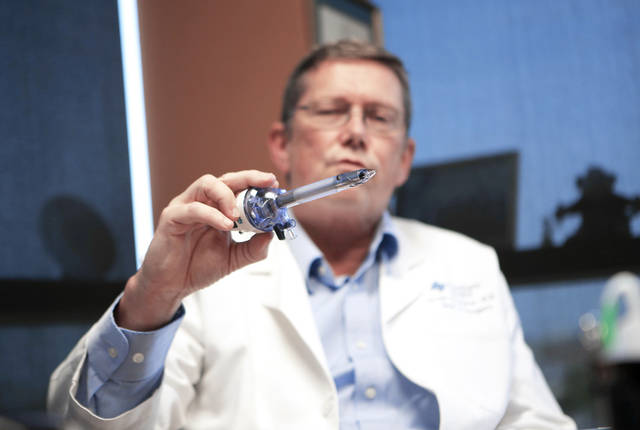 Dr. Svein M. Holsaeter, a surgeon at St. Anthony's Hospital, holds a laparoscopic port Thursday while he describes what it's like to have an appendectomy.  Photo by Garett Fisbeck, The Oklahoman