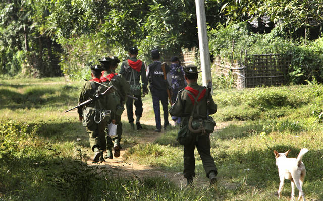 In this photo taken on Nov. 11, 2012, Myanmar army officers patrol as a dog follows them to Sin Thet Maw relief camp in Pauktaw township, Rakhine State, western Myanmar.  Myanmar�s government has launched a major operation aimed at verifying the citizenship of Muslims in western Rakhine state, the coastal territory that has been torn apart by Buddhist-Muslim violence since June.  Questions over whether the region's Muslim Rohingya population qualify for citizenship are at the heart of a crisis that has killed nearly 200 people and displaced 110,000 more.  (AP Photo/Khin Maung Win)