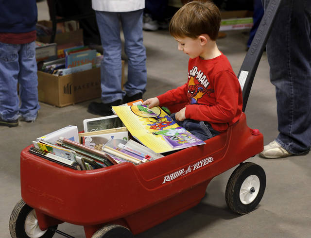 Reed Stephens, 4, Oklahoma City, reads some of his new books while riding through the building in a wagon pulled by his dad, Justin. Several thousand bibliophiles and bargain hunters crowded into Oklahoma Expo Hall at State Fair Park on Saturday, Feb. 23, 2013,  in a quest to find reading material  at deeply discounted  prices.  Friends of the Metropolitan Library System is holding their much-anticipated annual book sale this weekend. The sale continues Sunday from 9 a.m. to 5:30 p.m.   Photo by Jim Beckel, The Oklahoman