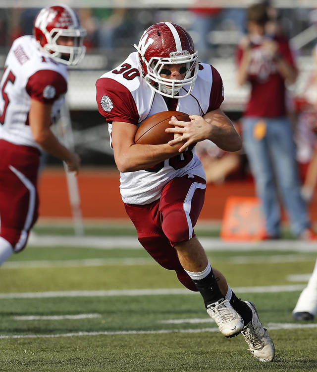 Wynnewood senior runningback B. J. Morris protects the ball as he cuts to the outside. In back is quarterback Jace Brown. Cashion vs. Wynnewood at Norman in a Class A semifinal football game, Saturday, Dec. 1, 2012.     Photo by Jim Beckel, The Oklahoman