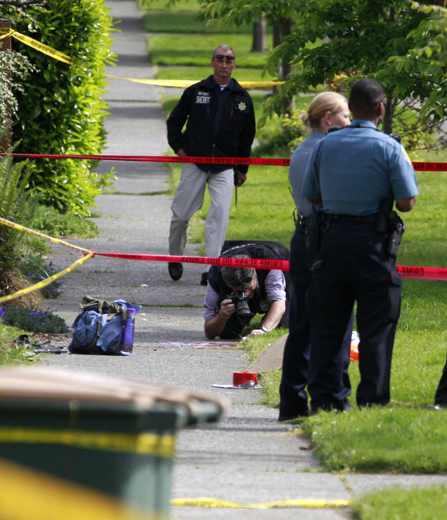 Police investigate the scene where a man who was believed to have shot and killed several people earlier in the day shot himself Wednesday, May 30, 2012, in the West Seattle neighborhood of Seattle. A gunman opened fire at a Seattle cafe earlier Wednesday, killing three people and critically wounding two others and later a man believed to be the same suspect shot and killed a woman and took her car near downtown, abandoning it less than two miles from where the alleged shooter shot himself as officers closed in on him, authorities said. His condition wasn't immediately known. (AP Photo/Elaine Thompson)