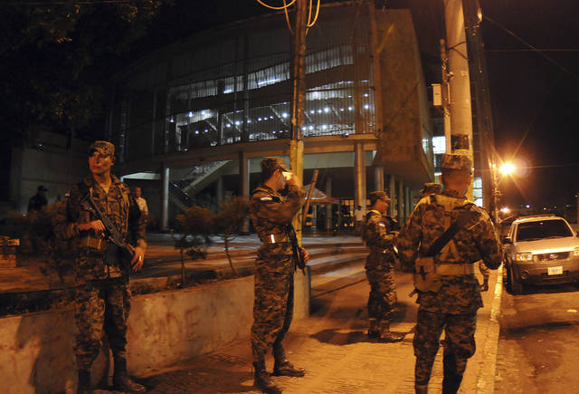 Honduras army soldiers stand guard outside of the National Congress in the capital city of Tegucigalpa, Honduras, Tuesday Dec. 11, 2012. The Honduran congress approved a bill Tuesday to submit President Porfirio Lobo's police cleanup program to a popular vote, after the measure was blocked by the courts. (AP Photo/Fernando Antonio)