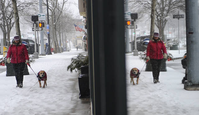 Danielle Kondratuk of Manchester walks her dog Bella as snow falls in Manchester, Conn., Friday, Feb. 8, 2013.  Snow began falling across the Northeast on Friday, ushering in what was predicted to be a huge, possibly historic blizzard and sending residents scurrying to stock up on food and gas up their cars. The storm could dump 1 to 3 feet of snow from New York City to Boston and beyond.  (AP Photo/Jessica Hill) ORG XMIT: CTJH108