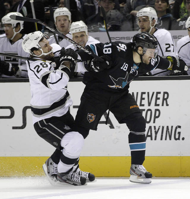 San Jose Sharks' Dominic Moore (18) is held by Los Angeles Kings center Jarret Stoll (28) during the first period of an NHL hockey game Saturday, April 7, 2012 in San Jose, Calif. (AP Photo/Marcio Jose Sanchez)