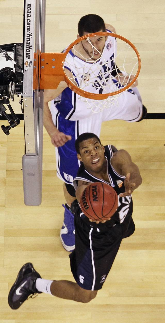 Butler's Ronald Nored (5) puts up a shot past Duke's Brian Zoubek during the first half of the men's NCAA Final Four college basketball championship game Monday, April 5, 2010, in Indianapolis. (AP Photo/Michael Conroy) ORG XMIT: FF140