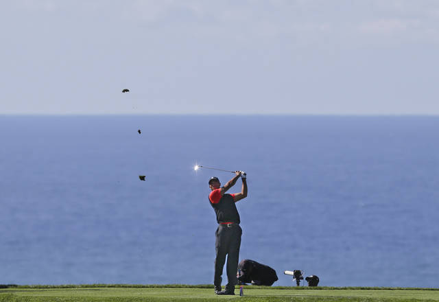 Tiger Woods sends divots flying as he tees off on the eighth hole of the South Course at Torrey Pines during the final  round of the Farmers Insurance Open golf tournament which he won Monday, Jan. 28, 2013, in San Diego. (AP Photo/Lenny Ignelzi)
