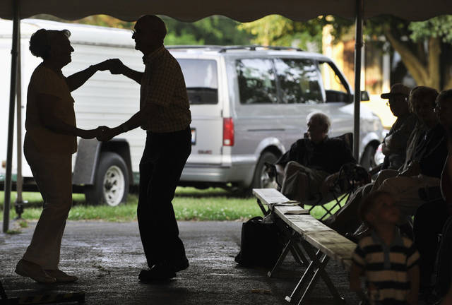 In this June 8, 2012 photo, Larry and Shirley Hackman, of Washington, Ill., dance in the shadow of the entertainment tent as the Jim Markum Swing Band plays at the Tremont Turkey Festival in Tremont, Ill. (AP Photo/Journal Star, Ron Johnson)