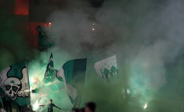 Panathinaikos' fans light flares during a Europa League group J soccer match against Lazio at the Olympic stadium of Athens, Thursday, Oct. 25, 2012. (AP Photo/Thanassis Stavrakis)