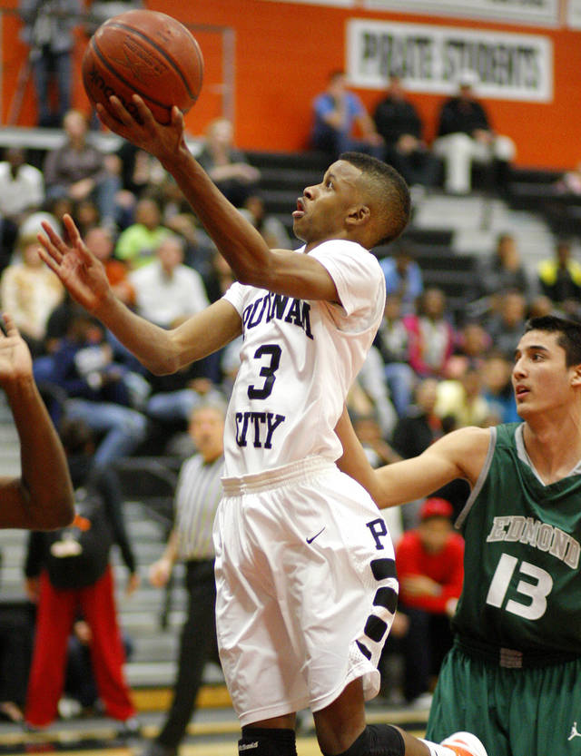 Putnam City's Ronnie Boyce goes past Edmond Santa Fe's Phoenix Bills during a high school basketball game at Putnam City in Oklahoma City, Tuesday, Feb. 7, 2012. Photo by Bryan Terry, The Oklahoman
