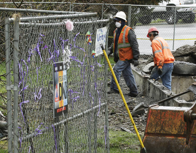 Purple ribbons left in tribute to Susan Cox Powell are shown on a fence as demolition workers from Pelland Enterprises work Wednesday, April 11, 2012, to remove what is left of the fire-damaged home where Susan's husband Josh Powell killed himself and his two sons on Feb. 5, 2012. in Graham, Wash. Susan Cox Powell, who went missing from their home in December 2009 in West Valley, Utah. (AP Photo/Ted S. Warren)