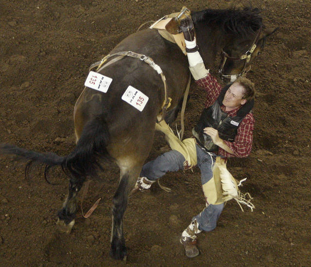 Brandon Holmes of Eva, Ala., falls off during the bareback riding competition in the PRCA National Circuit Finals Rodeo at the State Fair Arena on Friday.  Photo by Bryan Terry, The Oklahoman