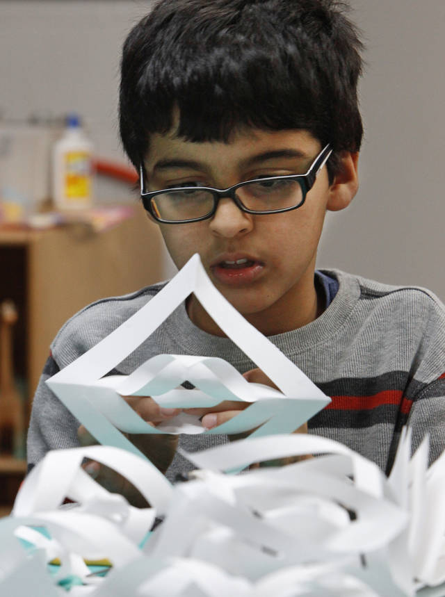Keon Moradi, 10, makes a snowflake to send to the students at Sandy Hook Elementary.  Photo By David McDaniel/The Oklahoman <strong>David McDaniel - The Oklahoman</strong>