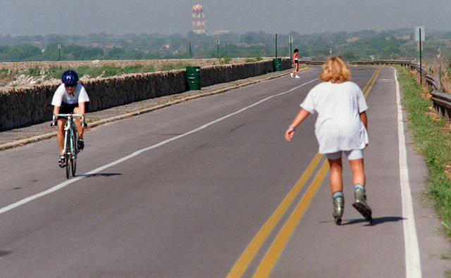 Bright, cool mornings at Lake Hefner also bring out the bike riders, roller bladers and joggers (rear) on the road atop the north side of the Lake Hefner dam.