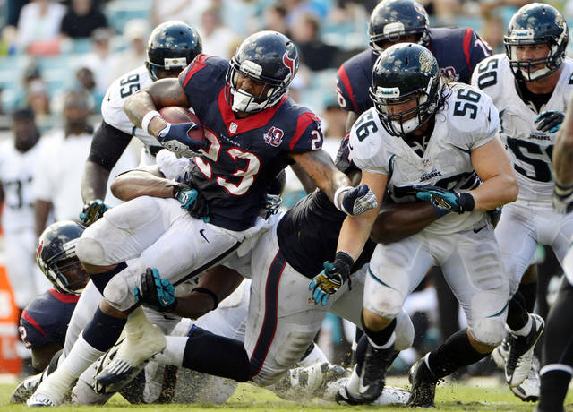 Houston Texans running back Arian Foster (23) gains yardage before being tackled by Jacksonville Jaguars outside linebacker Kyle Bosworth (56) and others during the second half of an NFL football game, Sunday, Sept. 16, 2012, in Jacksonville, Fla. Houston won 27-7. (AP Photo/Phelan M. Ebenhack)