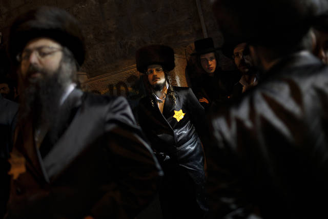 Orthodox Jewish men, wearing a Star of David patch similar to those the Nazis forced Jews to wear, attend a rally in Jerusalem's Mea Shearim neighborhood, Saturday, Dec. 31, 2011. Thousands of ultra-Orthodox Jews gathered to rally for the right to protect their way of life. (AP Photo/Bernat Armangue)