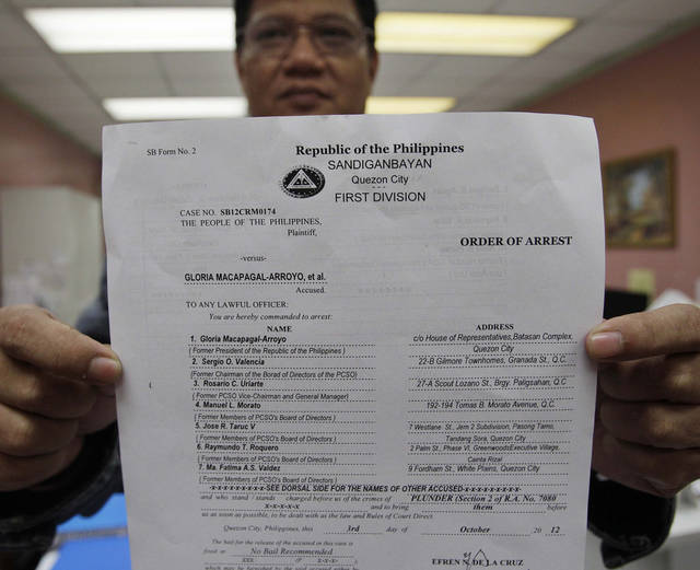 Sandiganbayan Executive Assistant Florecal Sebastian shows a copy of the Order of Arrest to former Philippine President Gloria Macapagal Arroyo at the Sandiganbayan anti-graft court in suburban Quezon City, north of Manila, Philippines, Thursday Oct. 4, 2012. The Philippine court has issued an order to arrest Arroyo on charges of plunder for allegedly misusing state lottery funds during her last years in office. (AP Photo/Aaron Favila)