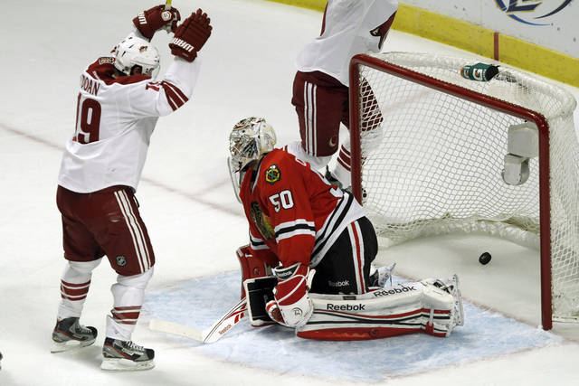 Phoenix Coyotes' right wing Shane Doan raises his arms after a Phoenix goal on Blackhawks' goalie Corey Crawford, right, as the Coyotes defeated the Chicago Blackhawks 4-0 in Game 6 of an NHL hockey Stanley Cup first-round playoff series in Chicago, Monday, April 23, 2012. (AP Photo /Daily Herald, Steve Lundy ) MANDATORY CREDIT