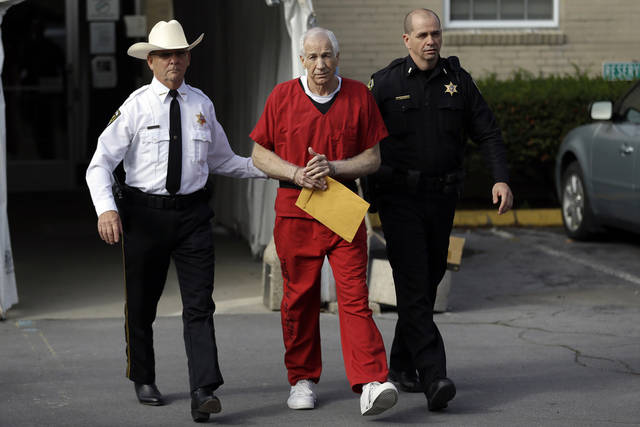 Former Penn State University assistant football coach Jerry Sandusky, center, is taken from the Centre County Courthouse by Centre County Sheriff Denny Nau, left, and a deputy, after being sentenced in Bellefonte, Pa., Tuesday, Oct. 9, 2012. Sandusky was sentenced to at least 30 years in prison, effectively a life sentence, in the child sexual abuse scandal that brought shame to Penn State and led to coach Joe Paterno's downfall. (AP Photo/Matt Rourke)