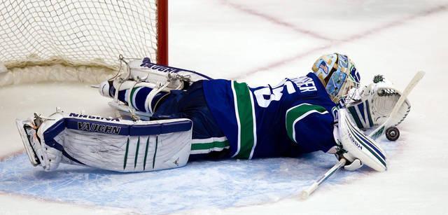 Vancouver Canucks' goalie Cory Schneider dives to cover up the puck against the Los Angeles Kings during the second period of game 5 of an NHL Western Conference quarterfinal Stanley Cup playoff hockey series in Vancouver, British Columbia on Sunday April 22, 2012. (AP Photo/The Canadian Press, Darryl Dyck)