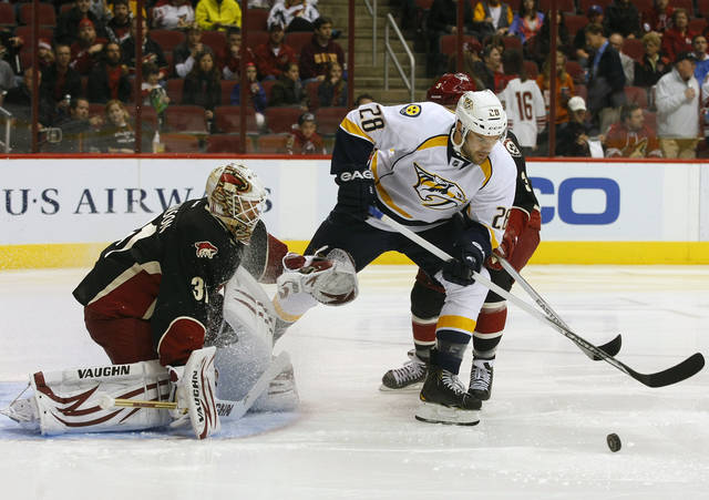 Nashville Predators center Paul Gaustad (28) looks to score on Phoenix Coyotes goalie Chad Johnson (31) in the first period during an NHL hockey game on Monday, Jan. 28, 2013, in Glendale, Ariz. (AP Photo/Rick Scuteri)