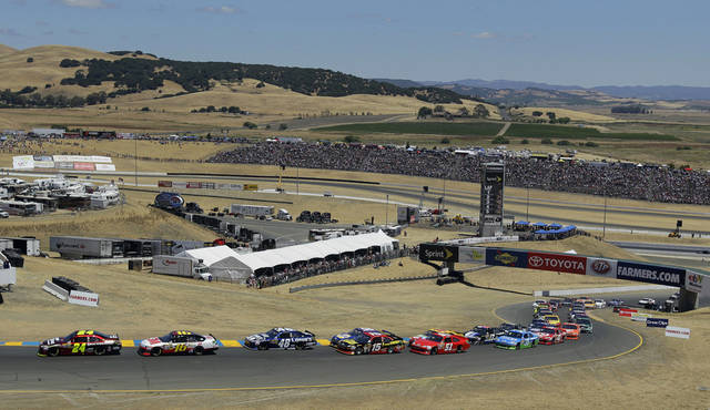 Drivers make their way up Turn 2 at the start of the NASCAR Sprint Cup Series auto race on Sunday, June 24, 2012, in Sonoma, Calif. (AP Photo/Eric Risberg)