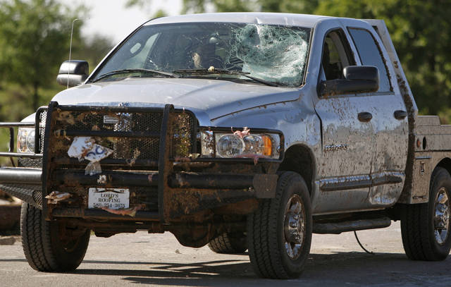 A truck with damage drives away from a damaged neighborhood in Woodward, Okla., Sunday, April 15, 2012. A tornado that killed five people struck Woodward, Okla., shortly after midnight on Sunday, April15, 2012.  Photo by Bryan Terry, The Oklahoman